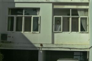 Eduardo na janela da sala de casa