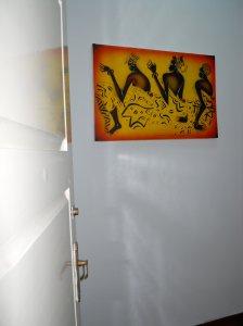 entrada de casa com porta aberta e quadro do Arun na parede