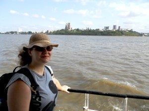 Sandra no barco, com Maputo ao fundo