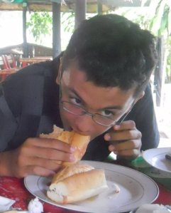 Guilherme abocanhando o sanduíche